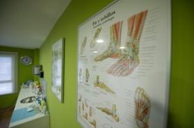 Póster de huesos y músculos del pie en la pared de la Clínica Escaño en Málaga